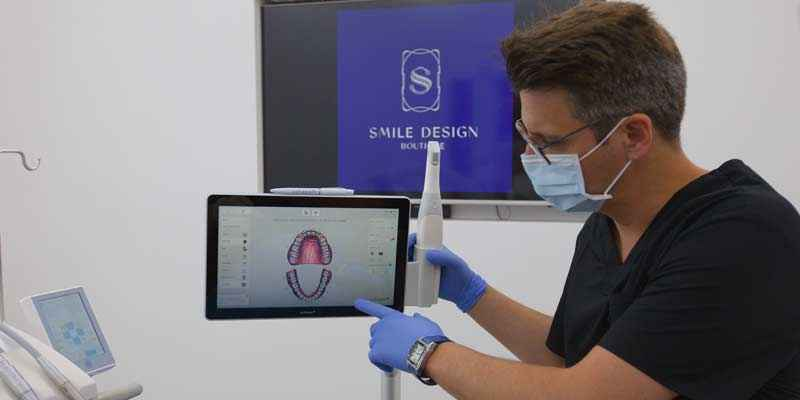 Dentist showing the new smile in 3D of a patient in Geneva