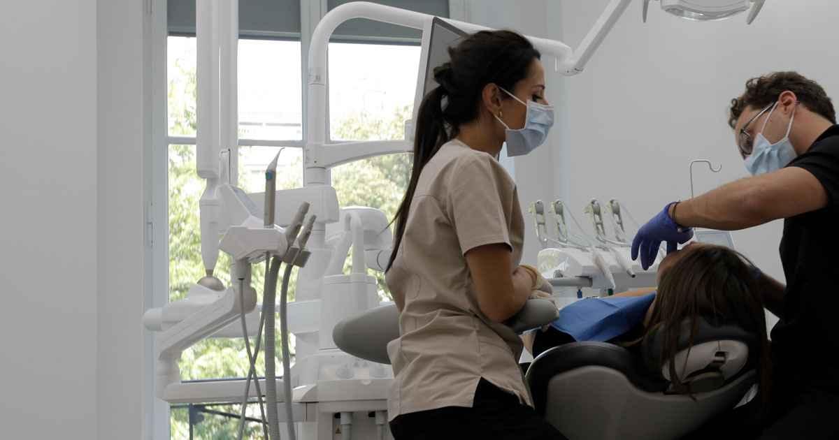 Un médecin et une assistante dentaire effectuent un blanchiment dentaire à un patient