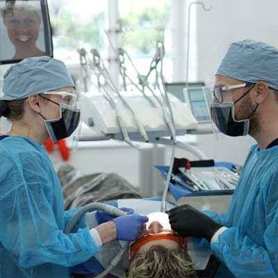 Un dentiste et une assistante dentaire mettent la dernière main au blanchiment dentaire d'un patient